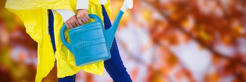Den sammansatta bilden av kvinnan i den gula regnrocken som rymmer bevattna kan arkivbild