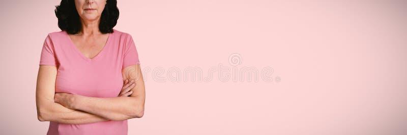 Den sammansatta bilden av kvinnor i rosa färger för bröstcancer korsar deras armar royaltyfria foton