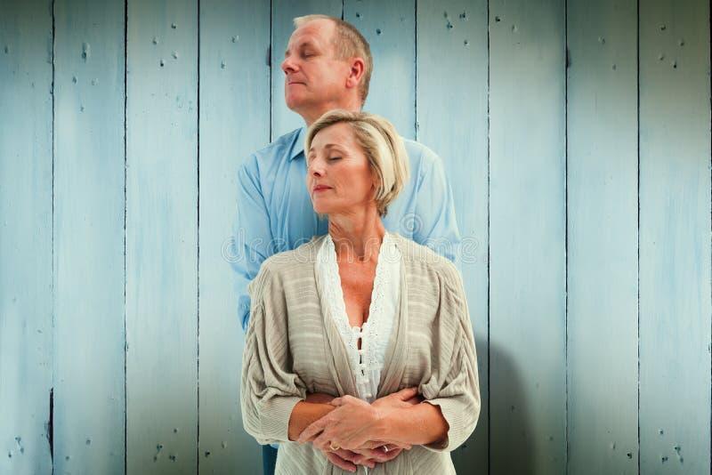 Den sammansatta bilden av lyckligt mognar par som omfamnar med stängda ögon royaltyfria bilder