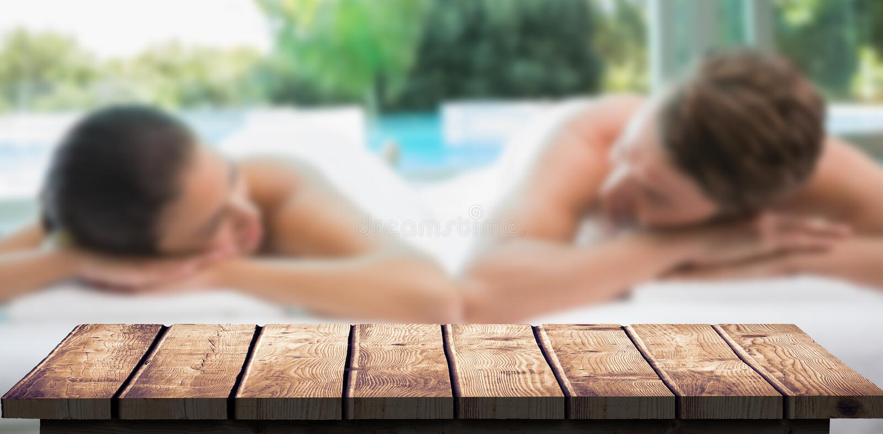 Den sammansatta bilden av par som ligger på massagetabellen på brunnsorten, centrerar arkivfoto