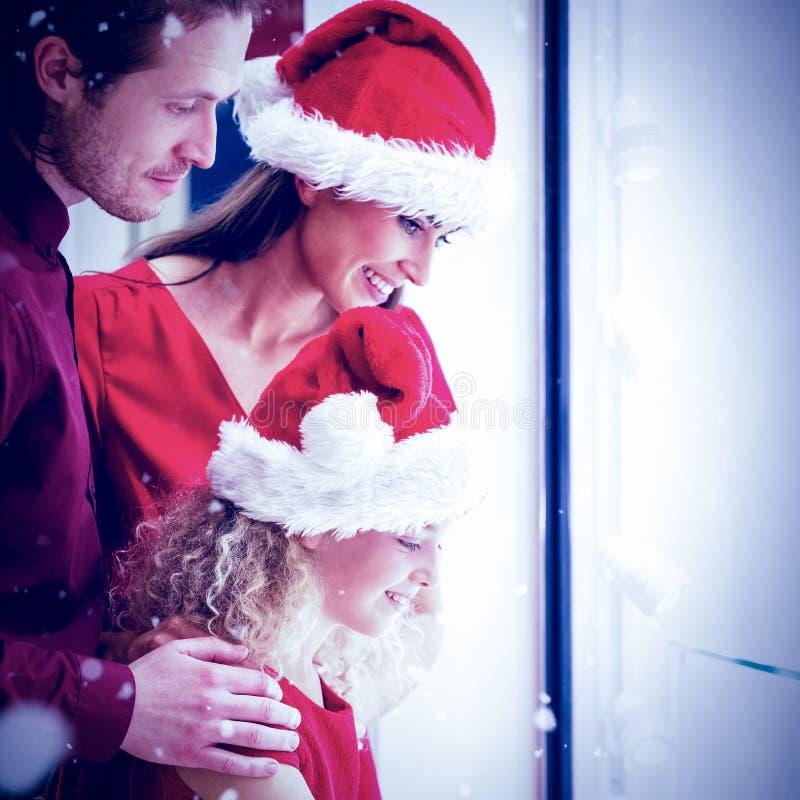 Den sammansatta bilden av sidosikten av familjen i jul klär att se skärm royaltyfri foto