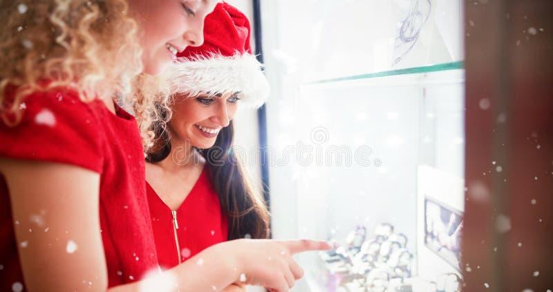 Den sammansatta bilden av sidosikten av modern och dottern i juldress som ser armbandsuret, displ royaltyfria bilder