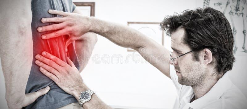 Den sammansatta bilden av sidosikten av en manlig fysioterapeut som undersöker, mans tillbaka royaltyfria foton