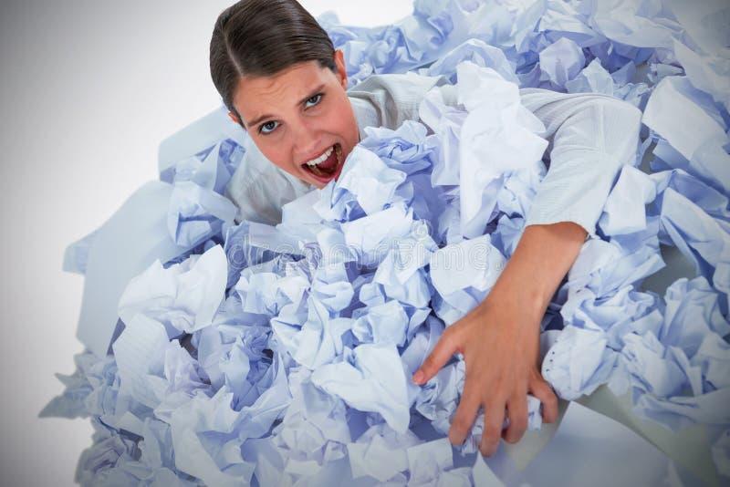Den sammansatta bilden av ståenden av den olyckliga affärskvinnan i hög skrynklade papper arkivfoto