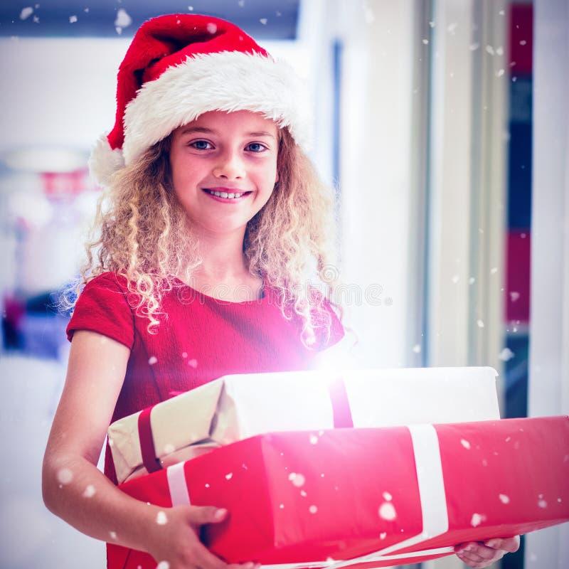 Den sammansatta bilden av ståenden av flickan i jul klär anseende med gåvor arkivfoton