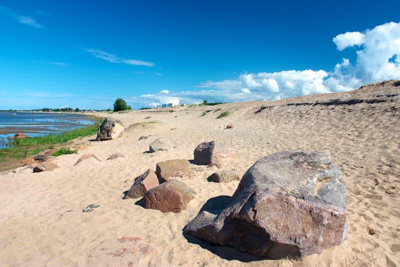 Den sandiga stranden med vaggar i Kalajoki royaltyfri fotografi