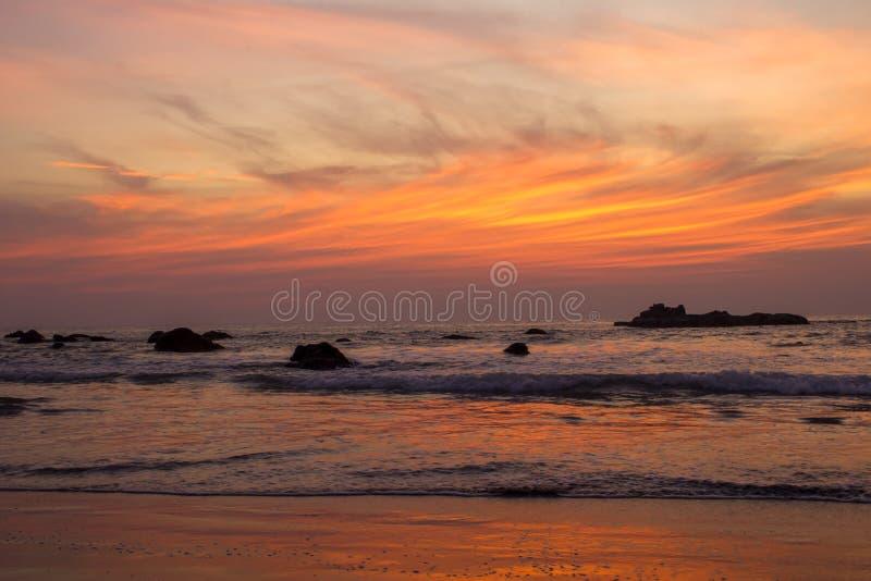 Den sandiga stranden på en bakgrund av havsvågor med vaggar under ljusa orange moln i en purpurfärgad solnedgånghimmel royaltyfria foton