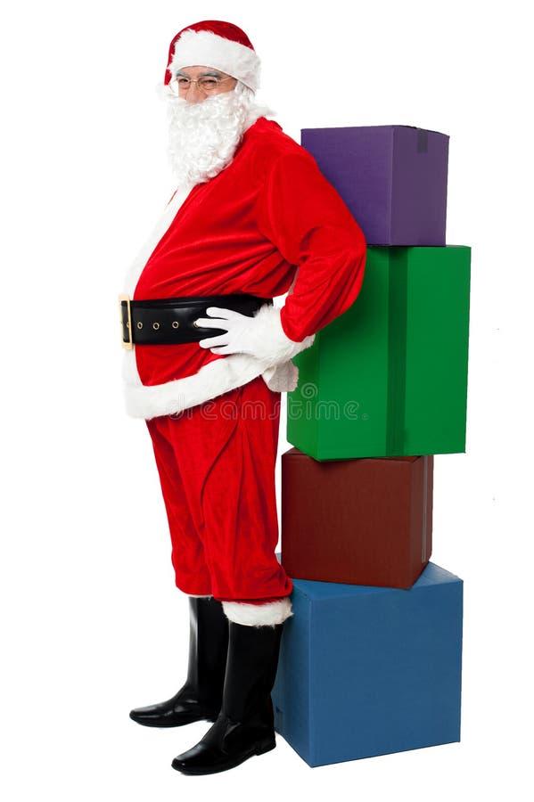 Den Santa benägenheten över färgrik stapel av Xmas presenterar royaltyfri foto