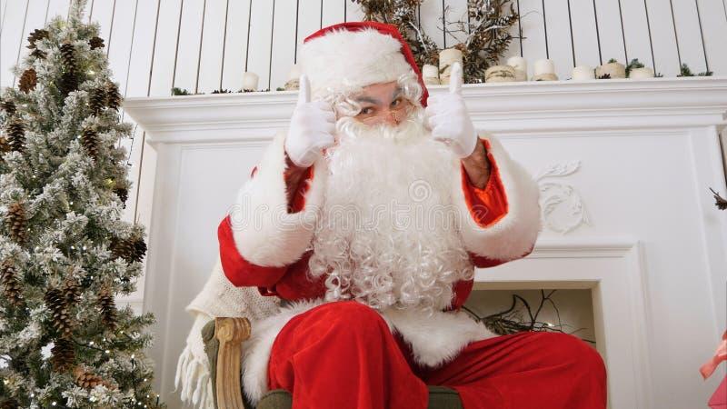 Den Santa Claus för lycklig jul visningen tummar upp royaltyfri foto
