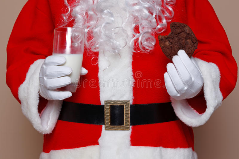 Den Santa Claus holdingen mjölkar och kakor royaltyfria foton