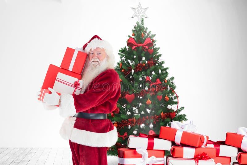 Den Santa Claus innehavbunten av gåvaaskar near julträdet arkivfoto