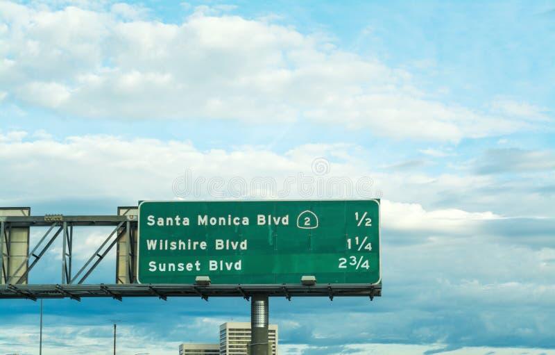 Den Santa Monica boulevarden undertecknar in en Los Angeles motorväg royaltyfria bilder