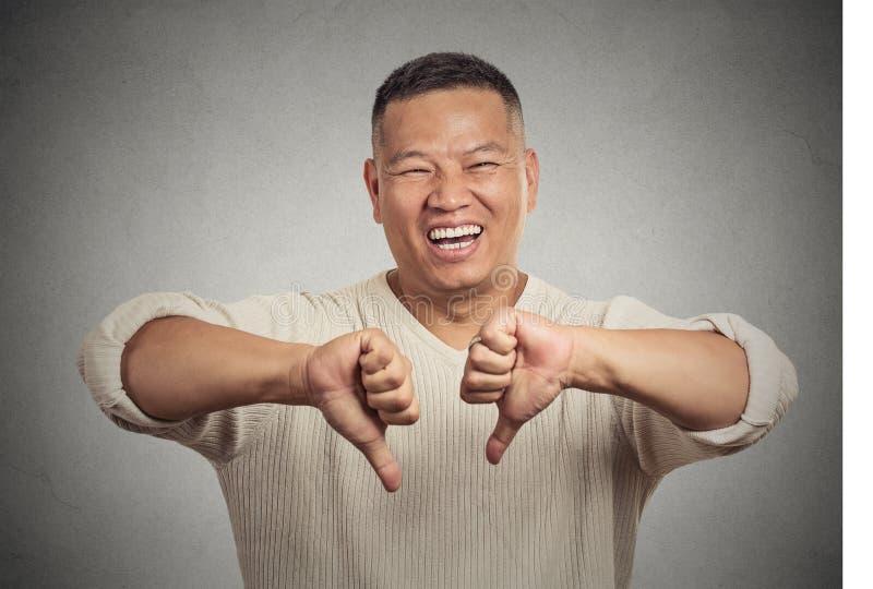 Den sarkastiska unga mannen som visar två tummar undertecknar ner, handgest fotografering för bildbyråer