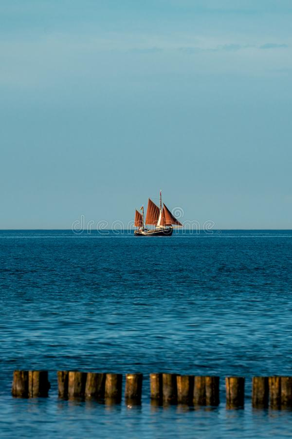 Den sceniska havbilden med en segelbåt med brunt seglar arkivbild