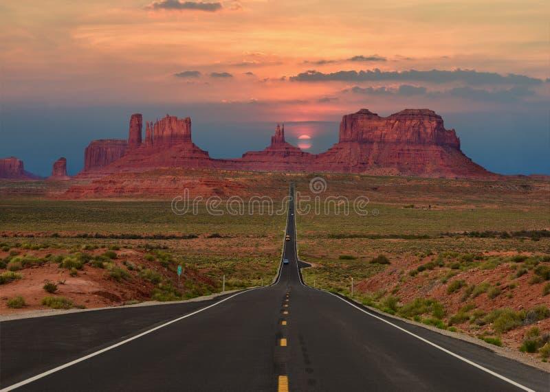 Den sceniska huvudvägen i den stam- monumentdalen parkerar i Arizona-Utah gräns, U S A ural town för bergsimsolnedgång fotografering för bildbyråer