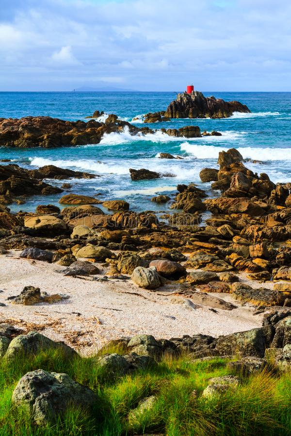 Den sceniska kustlinjen med vågor som sköljas upp på stranden på litet, vaggar öar royaltyfria foton