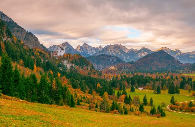 Den sceniska sikten av den alpina dalen med Neuschwanstein och Hohenschwangau rockerar på höstmorgonen arkivbilder