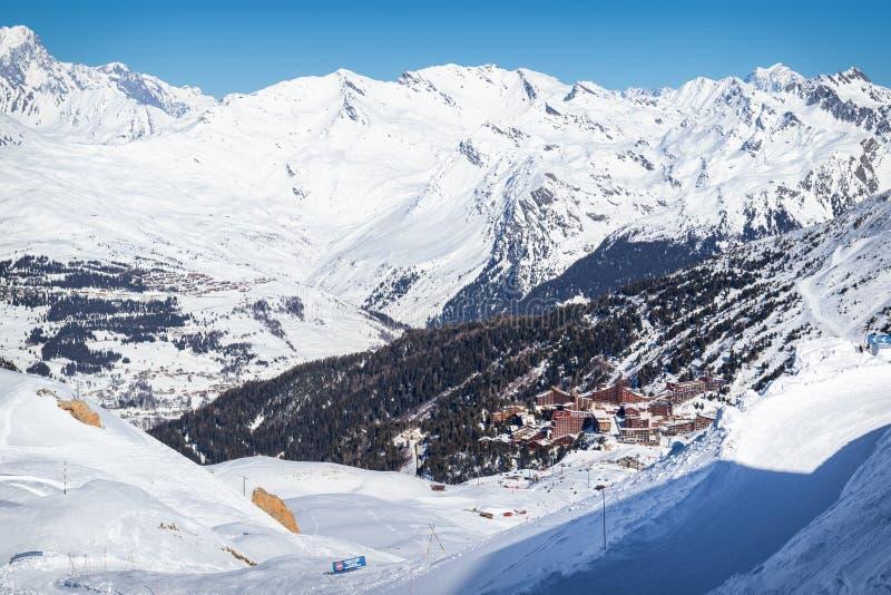 Den sceniska sikten av det populärt skidar semesterorten Les välvar i franska fjällängar Härlig solig dag med blå himmel arkivfoto