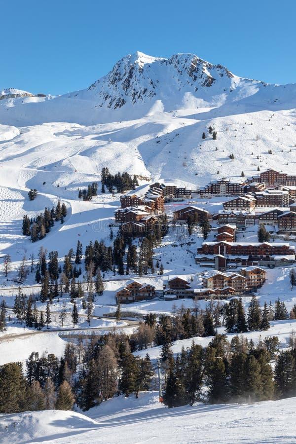 Den sceniska sikten av en hög höjd skidar semesterorten Belle Plagne i franska savojkålfjällängar på en härlig solig dag arkivbilder
