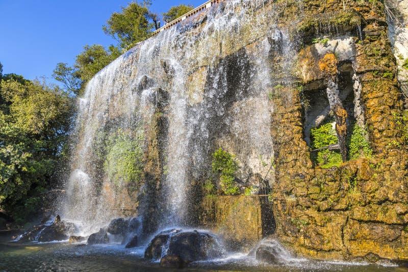 Den sceniska sikten av vattenfallet i slottkulle parkerar Parc de la Colline fotografering för bildbyråer