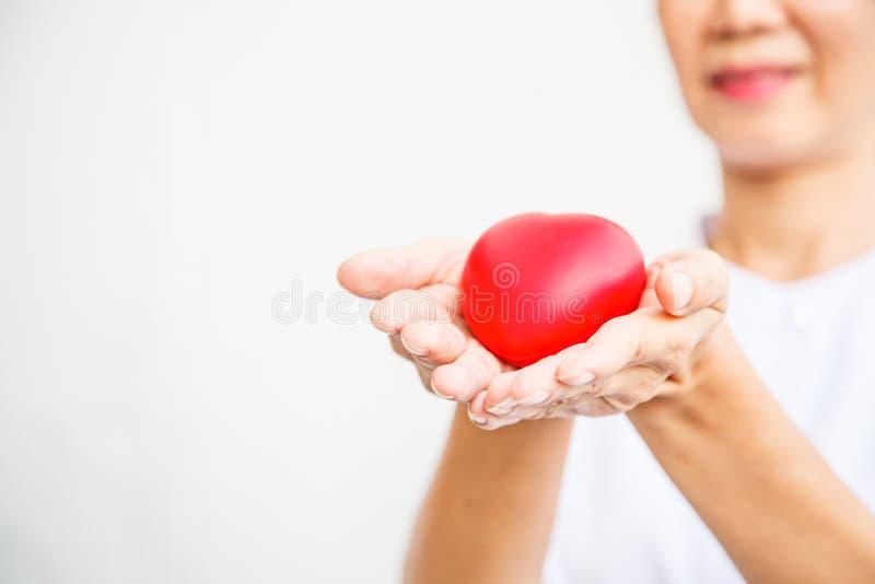 Den selektiva fokusen av röd hjärta rymde, genom att le kvinnlig sjuksköterska` s som båda räcker och att föreställa ge allt förs royaltyfri bild