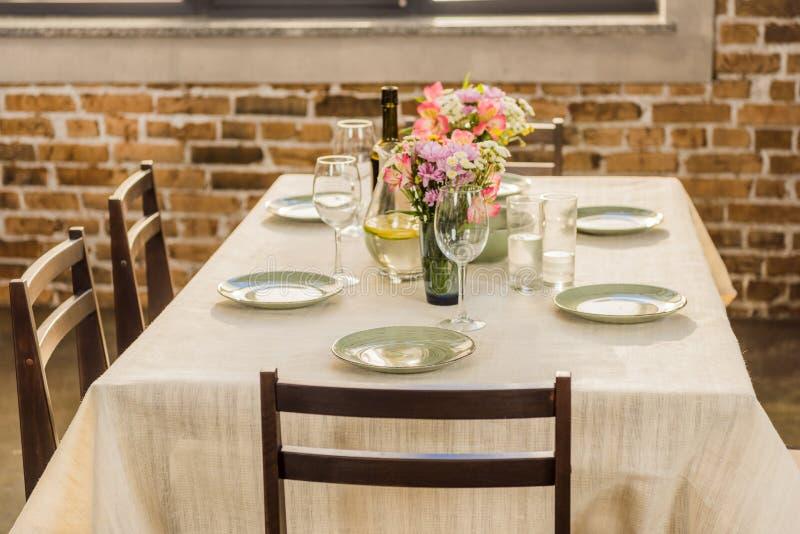 den selektiva fokusen av tabellen tjänade som med vinexponeringsglas, tömmer plattor och flaskan av vin royaltyfria bilder
