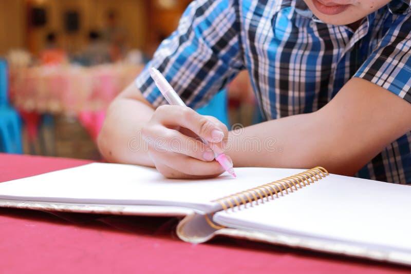 Den selektiva fokusen på händer av ung gästmanhandstil på minnesboken för att välsigna ord till nygifta personer kopplar ihop i b royaltyfri foto