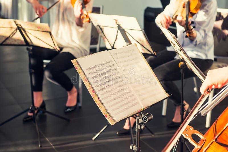 Den selektiva fokusen på musikanmärkningsark på ställning med bakgrund av att spela cellister och violinister sätter band på händ royaltyfri bild