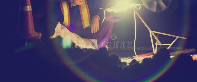 Den selektiva fokusen som ska riktas uppmärksamheten på, och byggnadsarbetaren arbetar på natten i konstruktionsplats med svart b royaltyfri fotografi