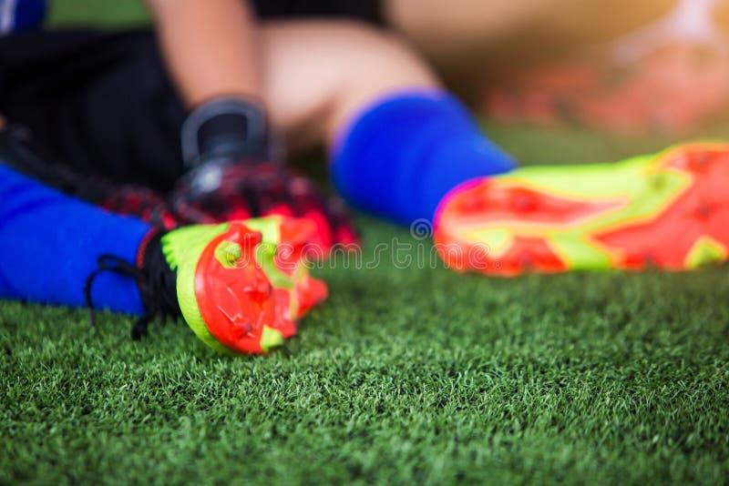 Den selektiva fokusen till målvakten sitter och fångar sular av foten på grund av smärtar, fotbollspelaren sårades i foten fotografering för bildbyråer