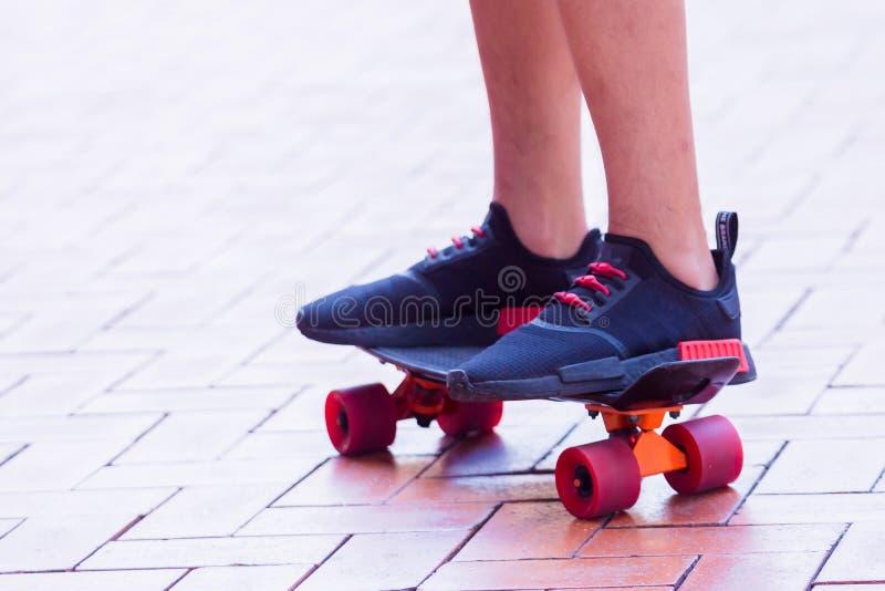 Den selektiva fokusen till pojkeskateboarderen är skateboarding och rida på gatan för röd tegelsten arkivbild