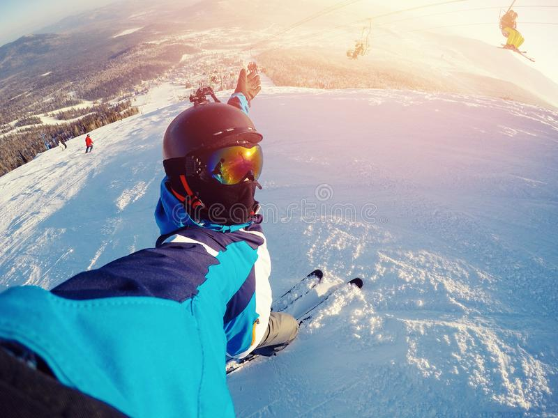 Den Selfie grabbidrottsmannen går på normal skidåkning skidar på lutningen med handlingkameran Sheregesh royaltyfri bild