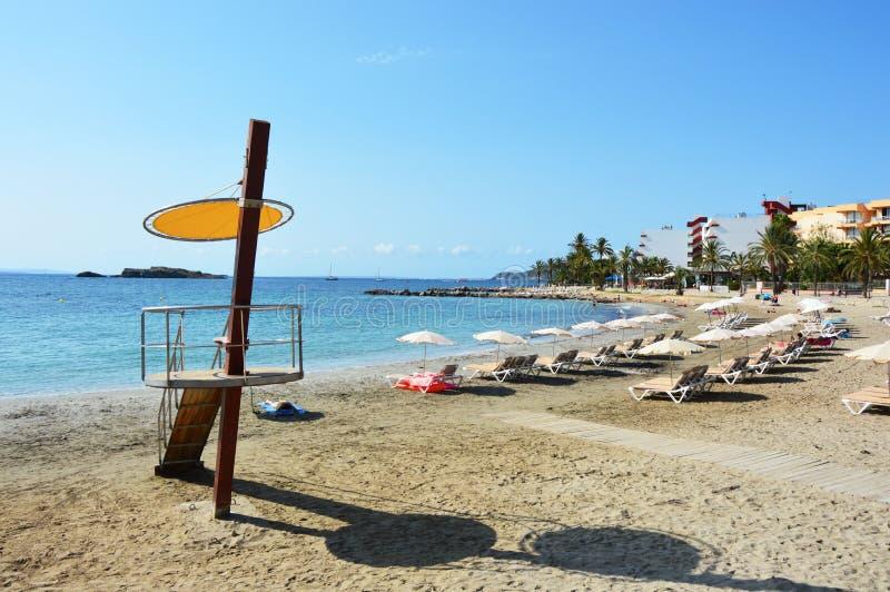 Den Ses Figueretes stranden med livräddaretornet och tömmer stranden utan personer, inga personer, med paraplyer sätter på land arkivfoto