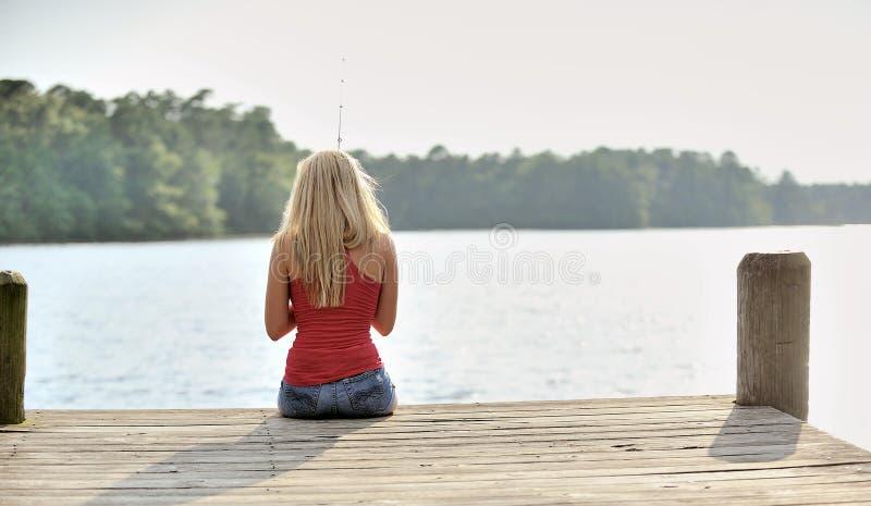 Den sexiga blonda kvinnan fiskar från skeppsdocka royaltyfri bild