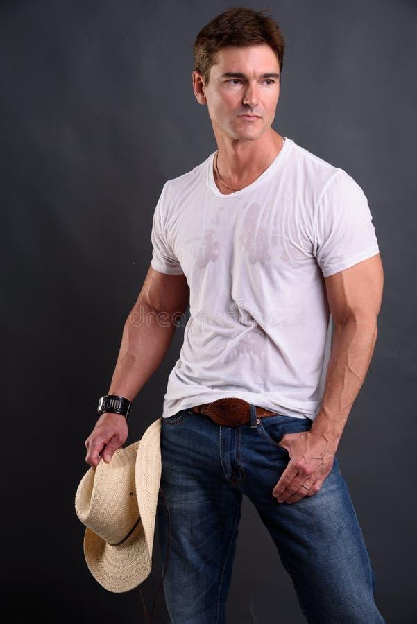 Den sexiga cowboyen ger en pyra blick royaltyfria bilder