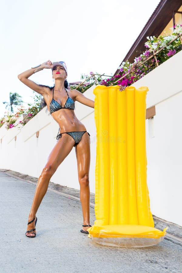 Den sexiga damen med långa ben near den vita väggen arkivbilder