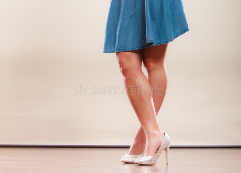 Den sexiga danskvinnan lägger benen på ryggen i höga häl och kjol royaltyfri fotografi