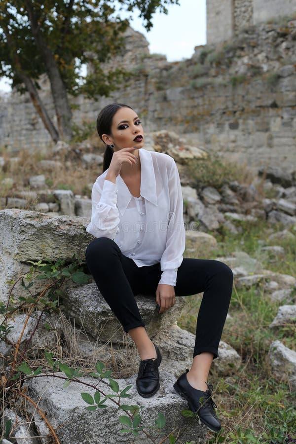 Den sexiga eleganta kvinnan med mörkt hår bär den vita skjortan, och svart flåsar royaltyfria foton