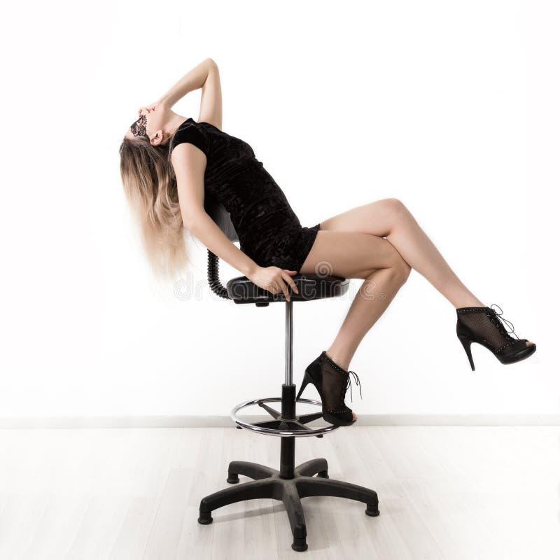 Den sexiga eleganta svarta klänningen för womanin poserar lite, medan sitta på en hög stol och fördela hennes ben flicka på a royaltyfria foton