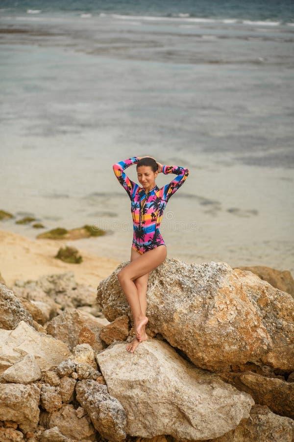 Den sexiga flickan som poserar sammanträde vaggar på, på stranden arkivbilder
