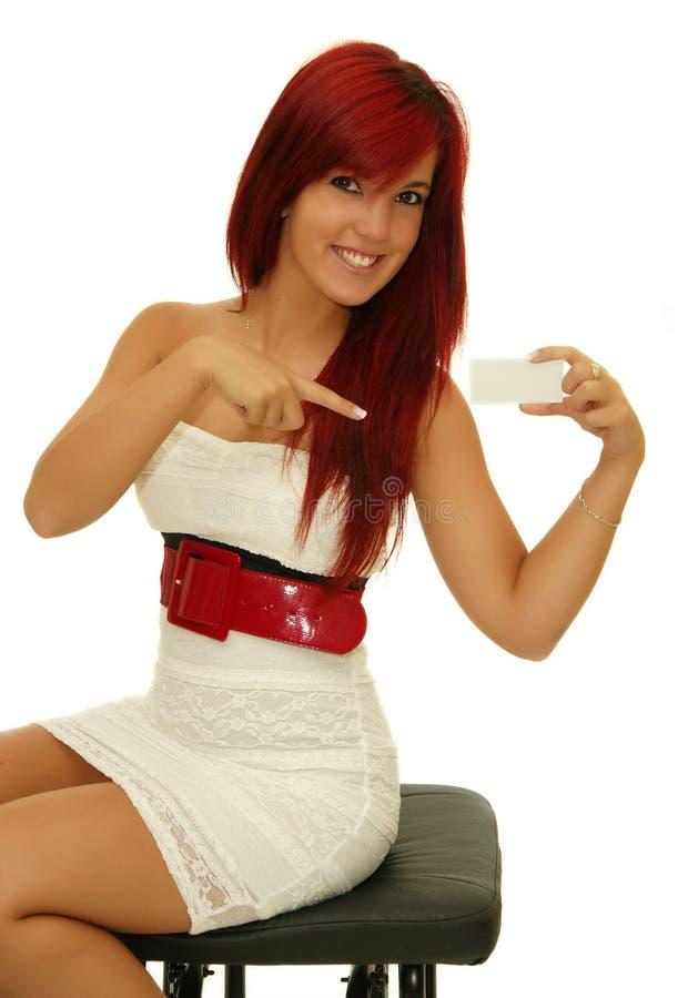 Den sexiga härliga le kvinnan som pekar på, undertecknar kortet royaltyfri foto