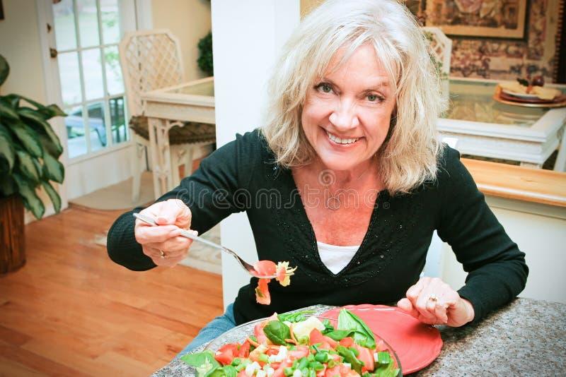 Den sexiga höga kvinnan äter sunt royaltyfri fotografi