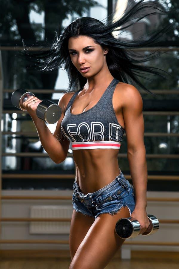 Den sexiga konditionbrunettkvinnan gör bicepskrullning med hantlar i idrottshallen arkivfoto