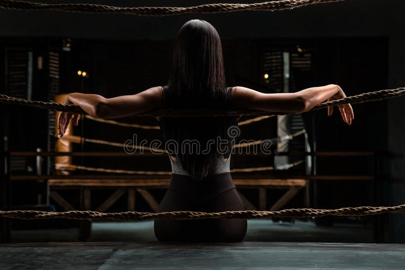 Den sexiga konditionbrunettkvinnan sitter tillbaka på cirkeln och vila för ask royaltyfri foto