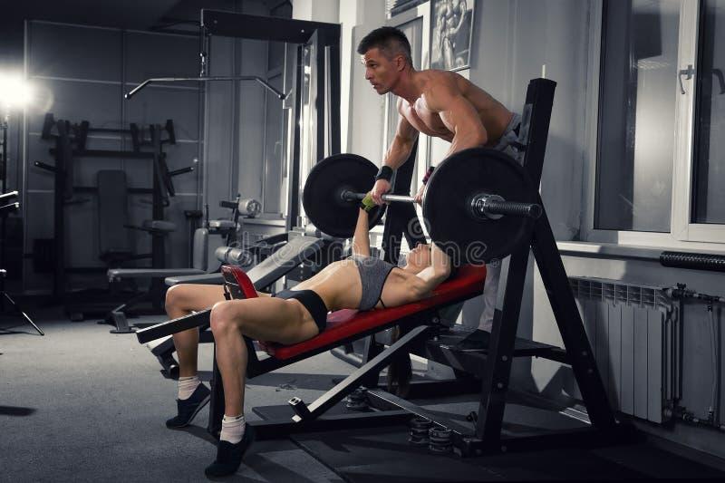 Den sexiga konditionflickagenomköraren med skivstången i idrottshallen, kvinnan och mannen i sport bär med den perfekta muskulösa royaltyfria foton