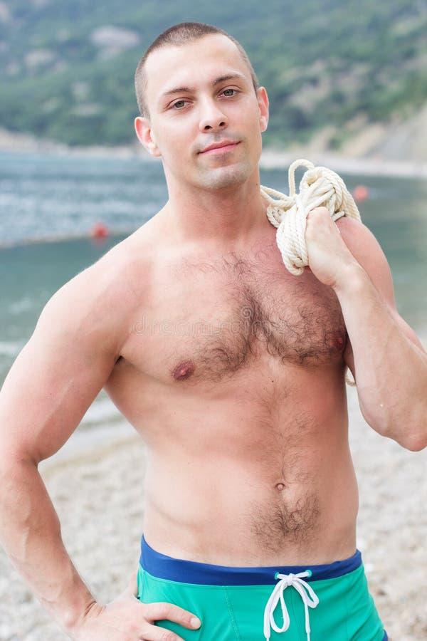 Den sexiga kroppbyggmästaren poserar på stranden royaltyfri fotografi