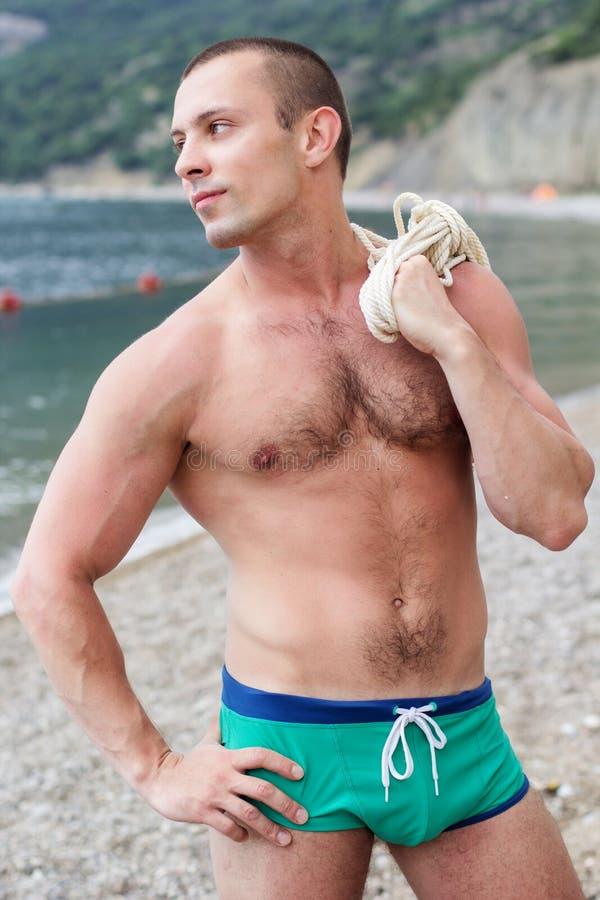 Den sexiga kroppbyggmästaren poserar på stranden royaltyfria foton
