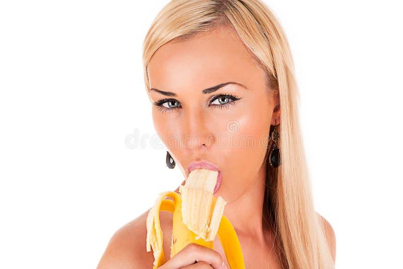 Den sexiga kvinnan äter bananen royaltyfria bilder