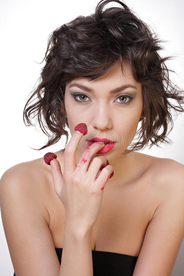Den sexiga kvinnan äter hallon royaltyfri foto