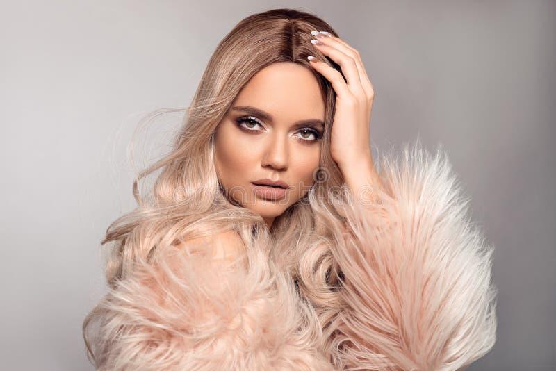 Den sexiga kvinnan bär i rosa pälslag Ombre blond frisyr Blond stående för skönhetmode Härlig flickamodell med makeup, länge fotografering för bildbyråer